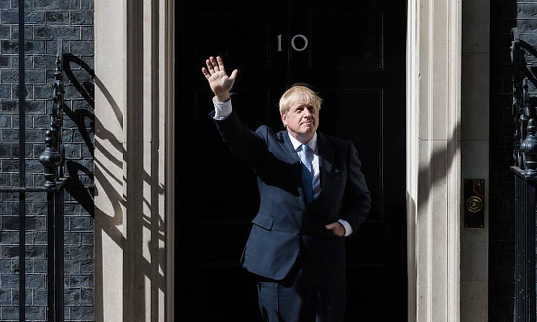 Boris Johnson acena diante da famosa porta preta da residência nº10 da Downing Street, a residência oficial do primeiro-ministro britânico, em Londres. Foto: WIktor Szymanowicz / NurPhoto via Getty Images
