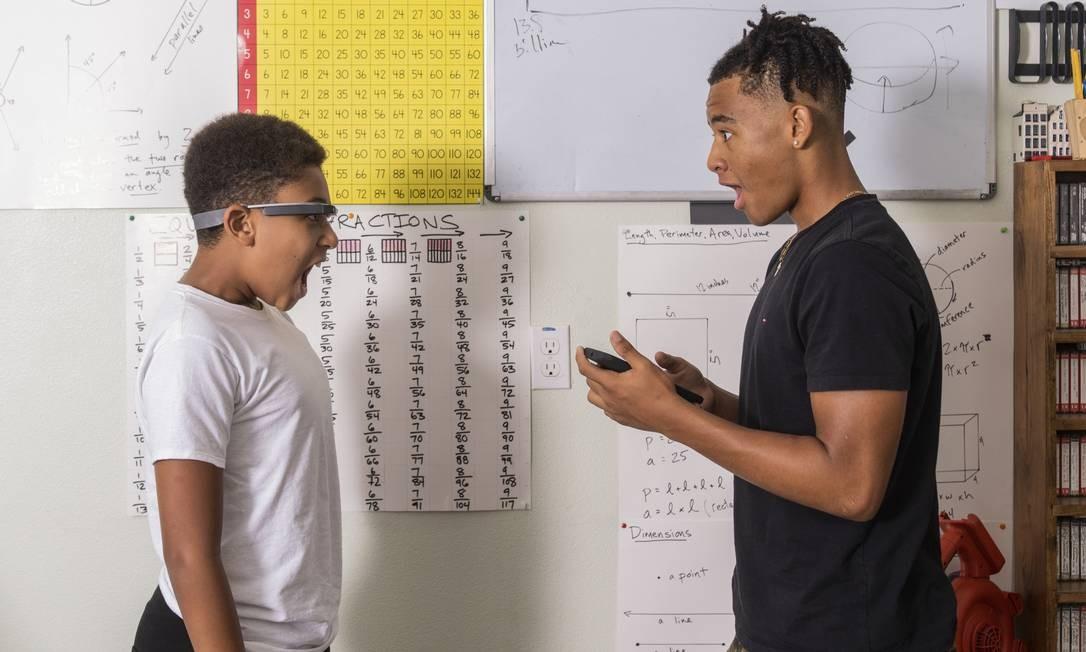 Esaïe Prickett, usando o Google Glass, pratica expressões faciais com o irmão Morgan, em casa, na Califórnia. Esaïe, que tem autismo, testa um aplicativo conectado ao óculos que o ajuda a reconhecer emoções Foto: CAYCE CLIFFORD / NYT