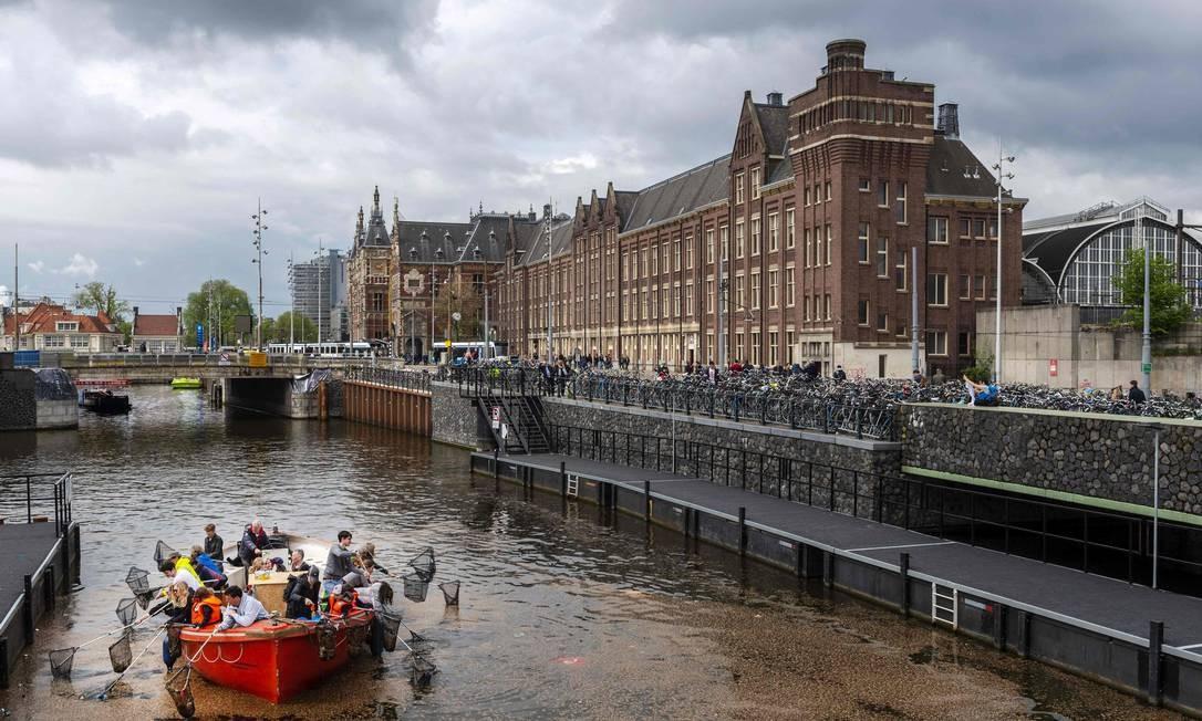 Turistas conhecem canais de Amsterdã pescando lixo Foto: Evert Elzinga/AFP / Evert Elzinga/AFP