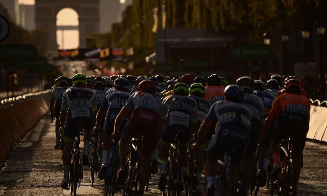 Ciclistas cruzam a Avenida Champs Elysées com o Arco do Triunfo ao fundo durante a 21ª e última etapa da 106ª edição da corrida de ciclismo Tour de France, entre Rambouillet e Paris, na França Foto: MARCO BERTORELLO / AFP