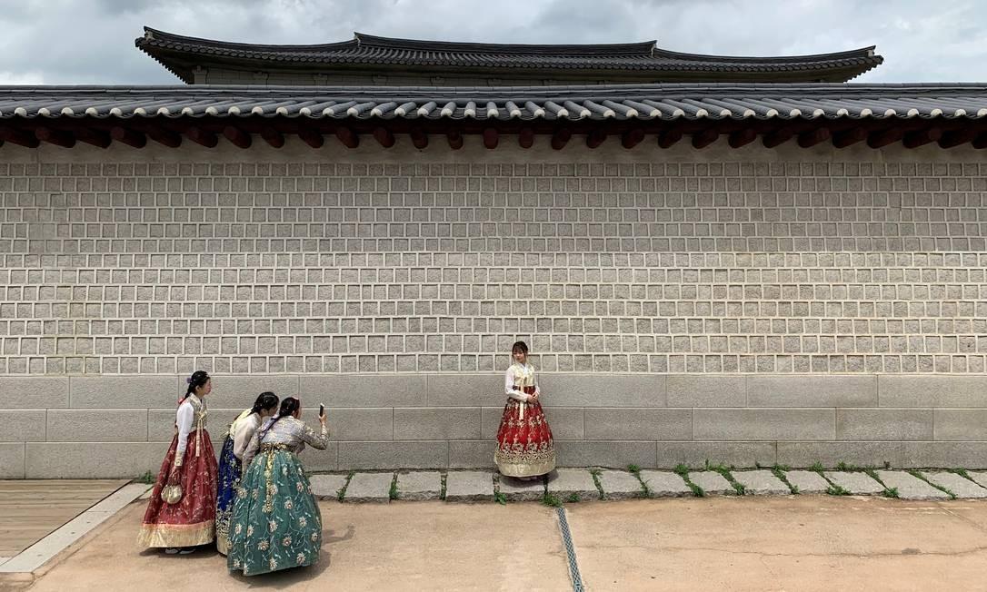 Turistas vestidos com trajes coreanos tradicionais tiram fotos durante visita ao Palácio Gyeongbokgung, em Seul, Coreia do Sul Foto: ANTONIO BRONIC / REUTERS