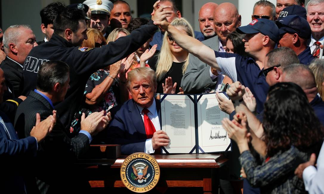 """Os primeiros socorristas de Nova York comemoram enquanto o presidente dos EUA, Donald Trump, apresenta a """"Autorização Permanente da Lei do Fundo de Compensação às Vítimas de 11 de setembro"""" durante uma cerimônia de assinatura no Jardim Rosa da Casa Branca, em Washington, EUA Foto: CARLOS BARRIA / REUTERS"""