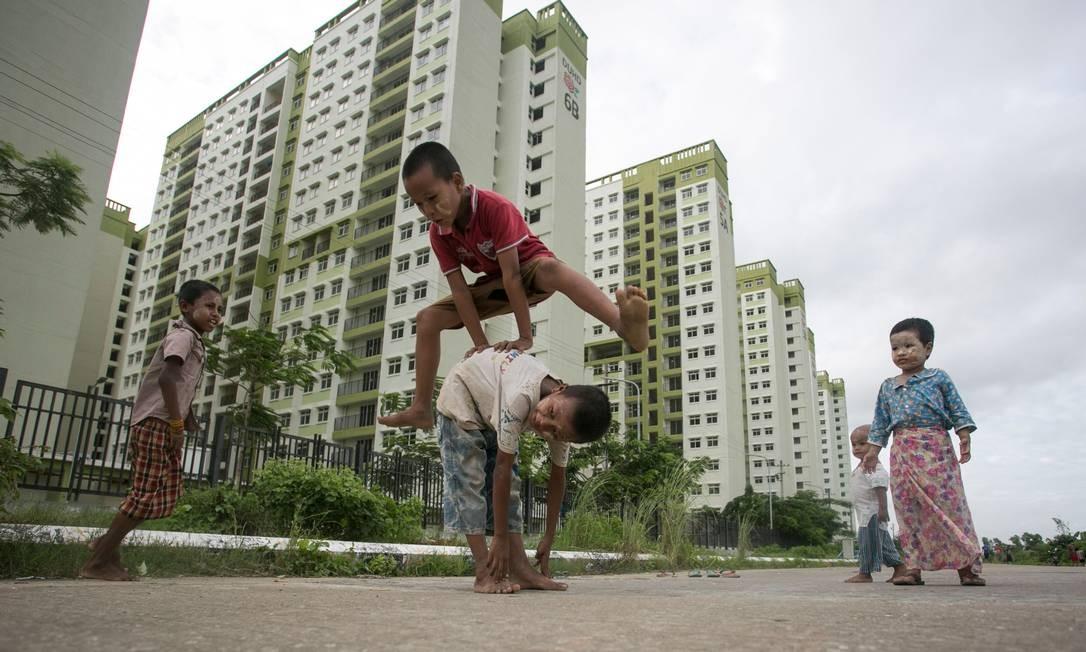Crianças brincam perto de um complexo de apartamentos nos arredores de Yangon, em Myanmar Foto: SAI AUNG MAIN / AFP