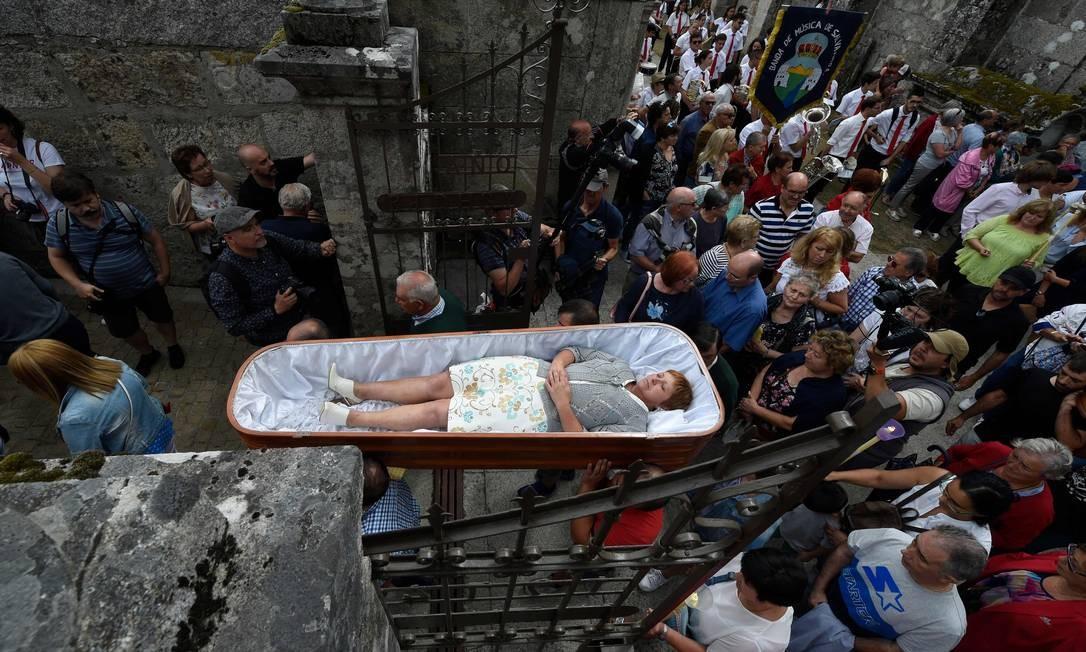 """Mulher é levada em um caixão por parentes durante a anual """"Procissão dos Mortos"""", em celebração à Santa Marta, conhecida como santa da ressurreição, na aldeia de Santa Marta de Ribarteme, noroeste da Espanha, perto de Nieves. Pessoas que escaparam da morte são carregadas em caixões e levadas em procissão por parentes em um gesto de gratidão por serem agraciadas com milagres que salvaram suas vidas Foto: MIGUEL RIOPA / AFP"""