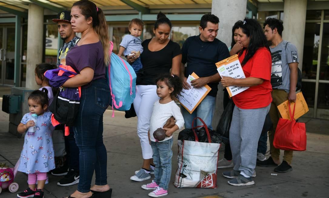Famílias de migrantes recém liberadas de centro de detenção esperam para embarcar em ônibus em McAllen, Texas: separações de crianças dos pais continua, apesar de ordem judicial contrária Foto: LOREN ELLIOTT/REUTERS