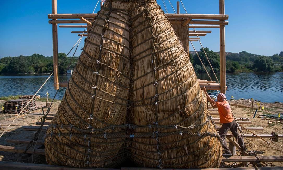 Membro da tripulação monta um barco de 14 metros de comprimento, na cidade de Beloslav, Bulgária. Uma equipe de pesquisadores e voluntários de oito países está se preparando para começar em meados de agosto uma jornada de 1.300 quilômetros para testar a hipótese de que as rotas comerciais pré-históricas atravessavam o alto-mar Foto: NIKOLAY DOYCHINOV / AFP