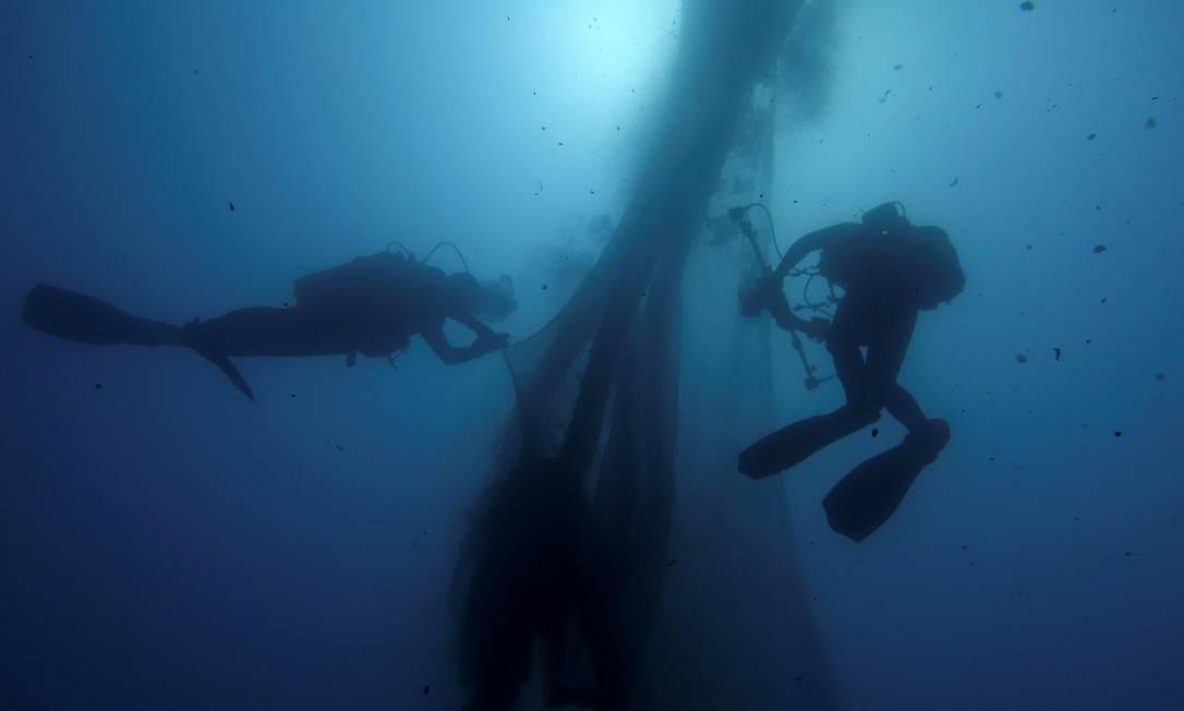 Mergulhadores voluntários do grupo ambiental Rebanho do Mar Egeu nadam ao lado de redes perdidas na ilha de Salamina, na Grécia Foto: STELIOS MISINAS / REUTERS