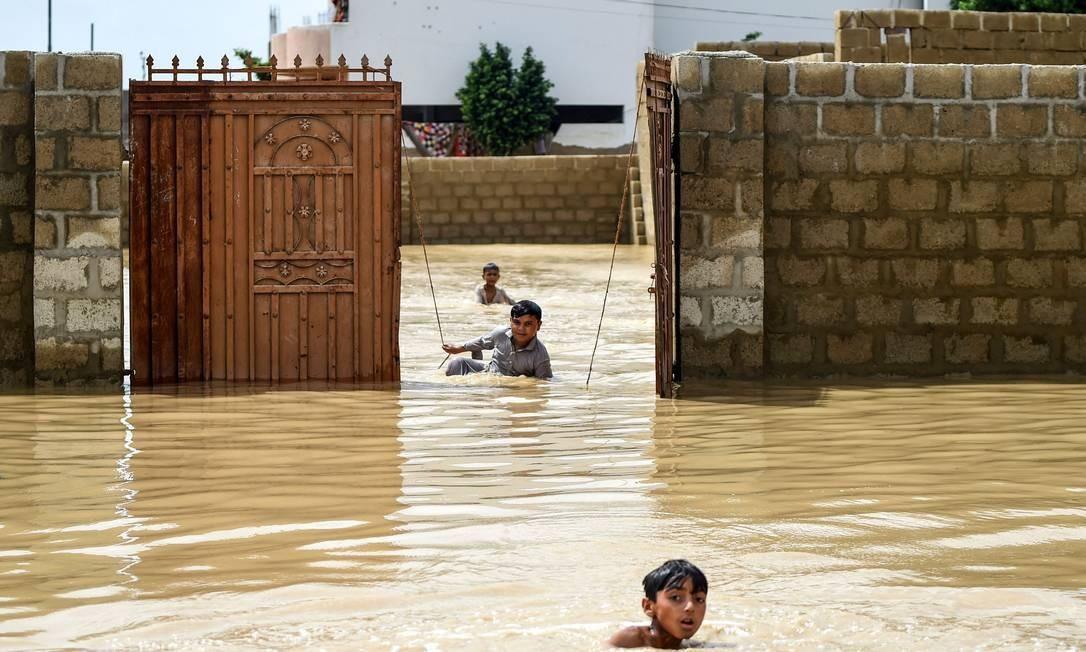 Meninos correm entre as enchentes durante as fortes chuvas de monção em Carachi, no Paquistão. Pelo menos 12 pessoas morreram na cidade portuária Foto: RIZWAN TABASSUM / AFP