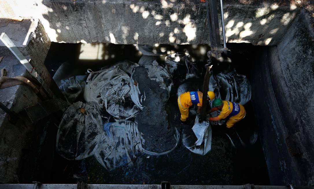 Funcionários da prefeitura trabalham na limpeza e reparo da comporta Foto: Pablo Jacob / Agência O Globo