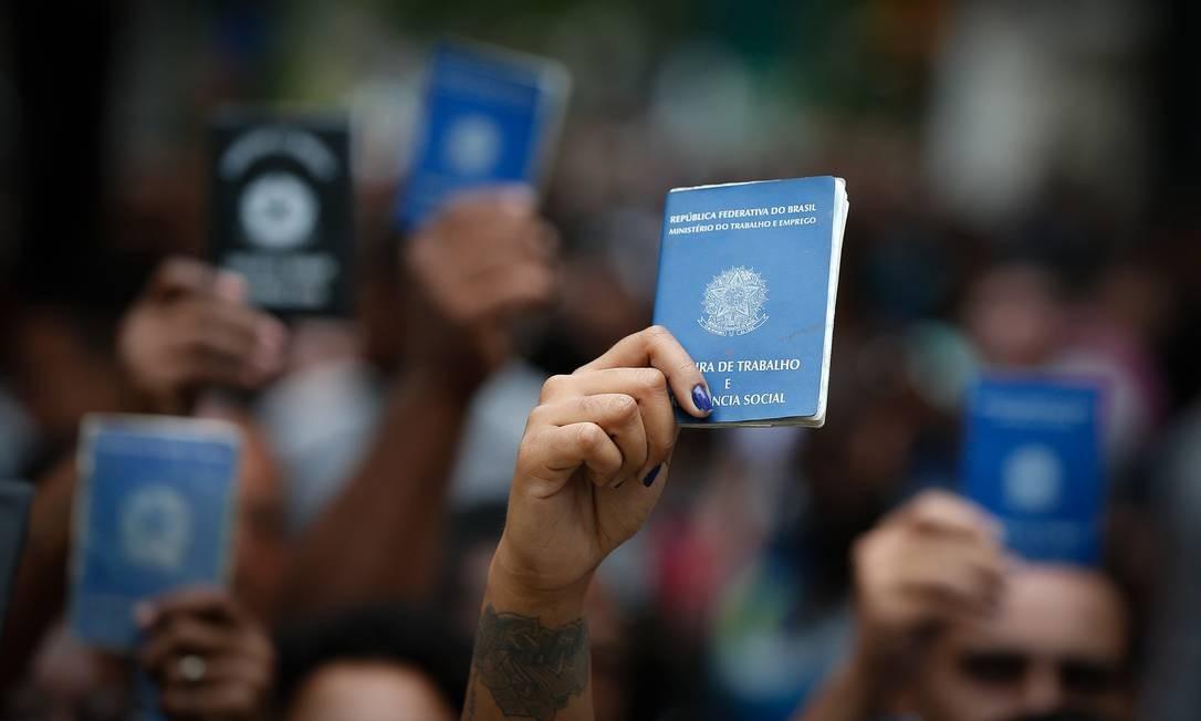 Trabalhadores erguem carteiras de trabalho em fila de emprego na Tijuca, Zona Norte do Rio, em abril: geração de vagas começa a melhorar. Foto: Pablo Jacob / Agência O Globo