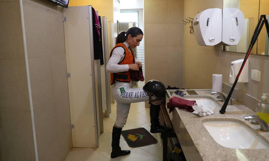 Alves organiza seu capacete de equitação, dentro do vestiário feminino, enquanto se prepara para um dia de corrida Foto: AMANDA PEROBELLI / REUTERS