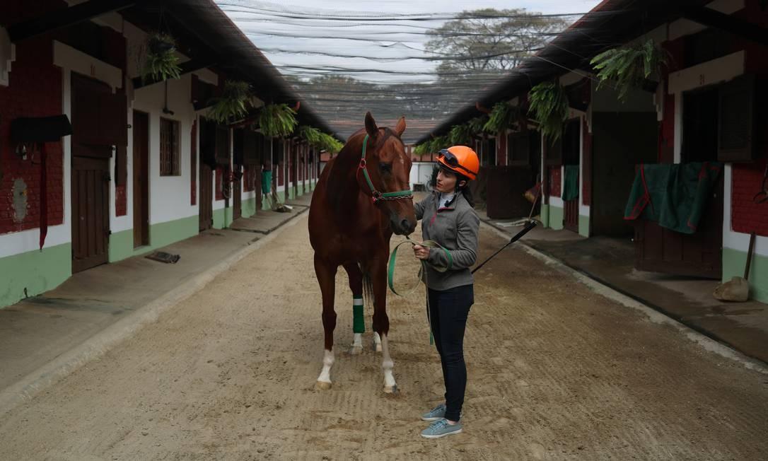 Jeane Alves posa junto a um cavalo chamado Rasgado. Nascida em Acopiara, interior do Ceará, a joqueta tomou gosto pela modalidade por conta do amor aos cavalos Foto: AMANDA PEROBELLI / REUTERS