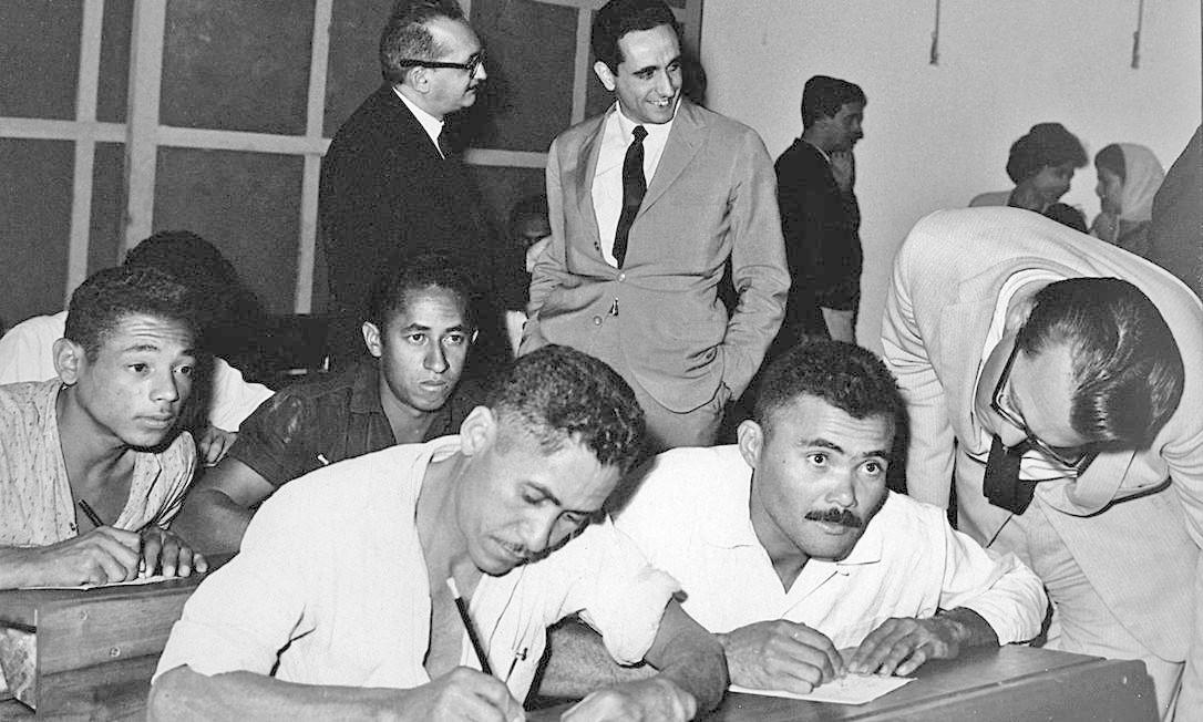 Paulo Freires (ao fundo, de óculos) em 1963, com alfabetizandos em Brasília Foto: Divulgação