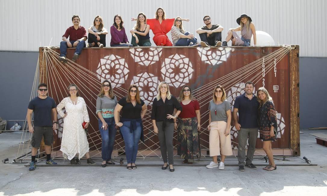 Equipe. Valéria Lopes de laranja ao centro e alguns dos profissionais que assinam os oito contêineres Foto: Fábio Guimarães / Divulgação