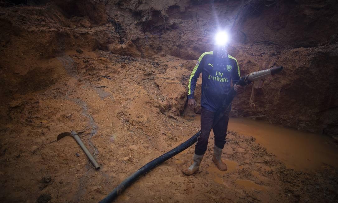 Garimpeiro com a caneta, mangueira de água usada para a escavação da terra Foto: Daniel Marenco / Agência O Globo
