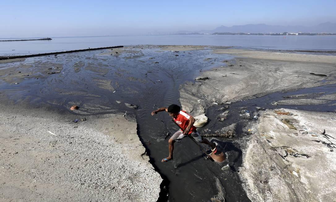 Na Praia de São Bento, na Ilha do Governador, morador tenta desviar de esgoto que corre a céu aberto Foto: Custódio Coimbra / Agência O Globo