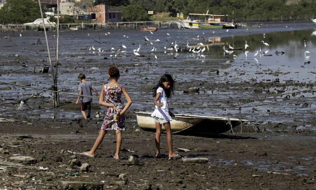 Mesmo contaminado pelo esgoto, crianças brincam na Praia de Tubiacanga, na Ilha do Governador Foto: Custódio Coimbra / Agência O Globo