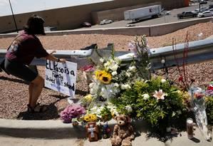 Mulher coloca um cartaz no local do ataque a tiros em El Paso, Texas: 20 mortos Foto: JOSE LUIS GONZALEZ / REUTERS