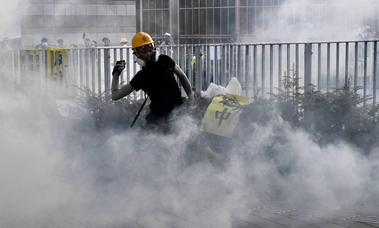 Um manifestante joga de volta a bomba de gás lançada pela polícia Foto: ANTHONY WALLACE / AFP