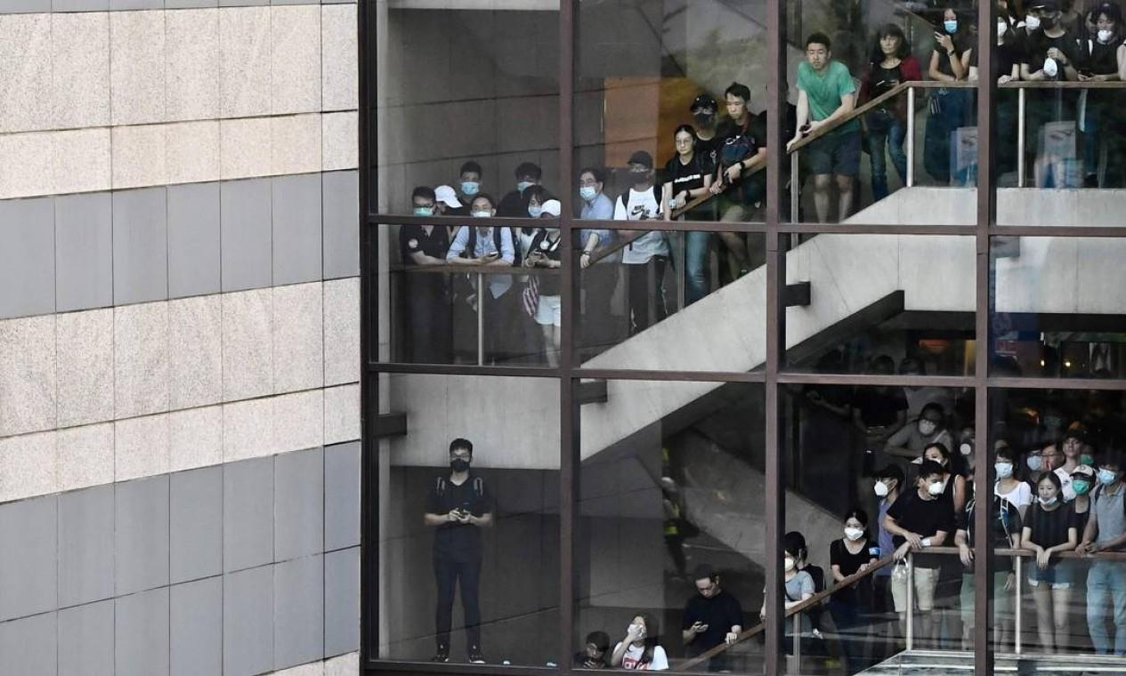 Pessoas assistem de um prédio a manifestantes enfrentando a polícia na área do Almirantado, onde ficam prédios do governo local Foto: ANTHONY WALLACE / AFP