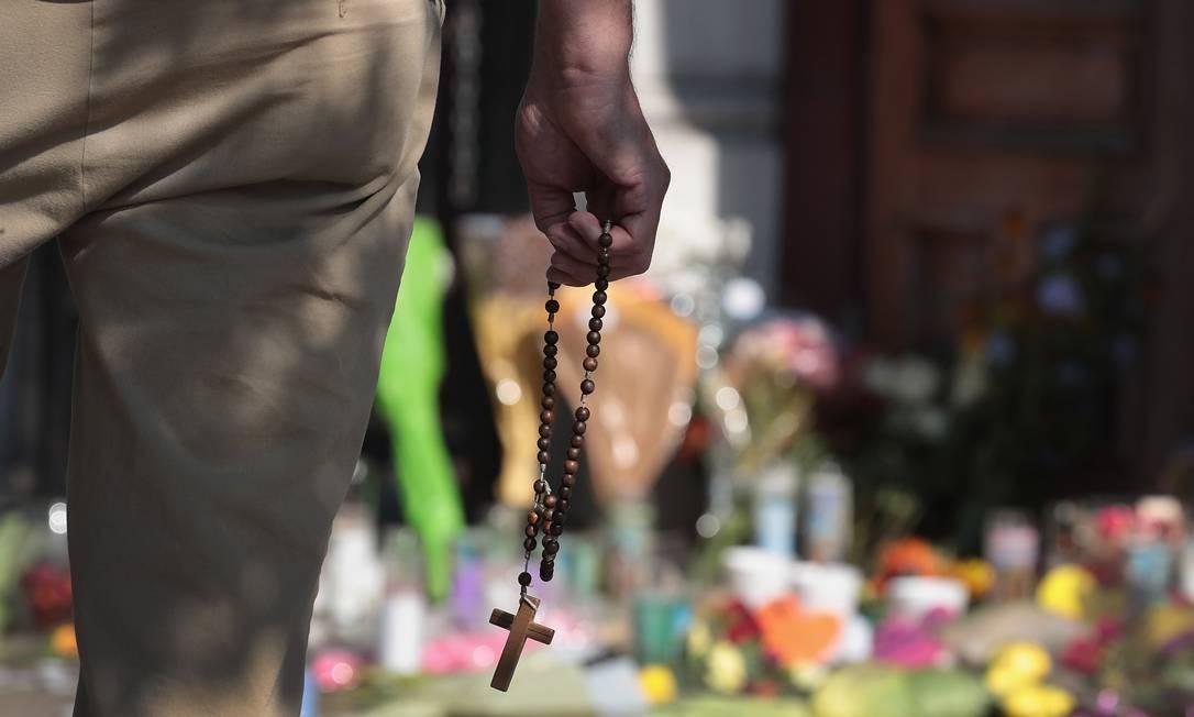 Homem segura um terço próximo ao memorial em homenagem às vítimas do massacre em Dayton Foto: SCOTT OLSON / AFP