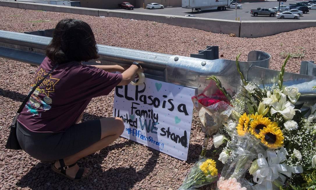 Mulher coloca uma placa ao lado de um memorial improvisado, em frente ao local do massacre no Texas. O atirador, Patrick Crusius, 22 anos, publicou na internet um manifesto em que defendia a supremacia branca no país e atacava a imigração Foto: MARK RALSTON / AFP