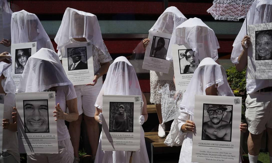 Manifestantes vestidas de branco seguram fotos das vítimas da violência na Times Square em resposta aos recentes ataques em massa em El Paso e Danton. Dos 22 mortos em El Paso, oito eram mexicanos Foto: Go Nakamura / AFP