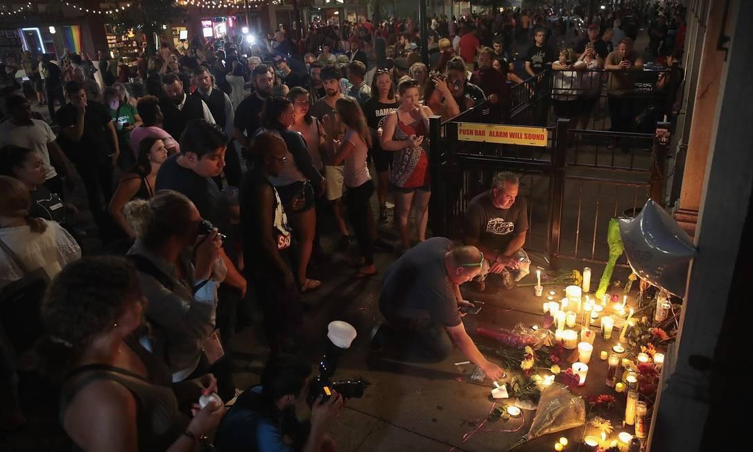 Pessoas deixam flores e velas na entrada do bar Ned Peppers, no distrito de Oregon, em Dayton, Ohio, onde um homem identificado como Connor Betts, 24 anos, abriu fogo com um rifle estilo AR-15 matando nove pessoas no domingo. Outras 27 vítimas do ataque ficaram feridas Foto: SCOTT OLSON / AFP