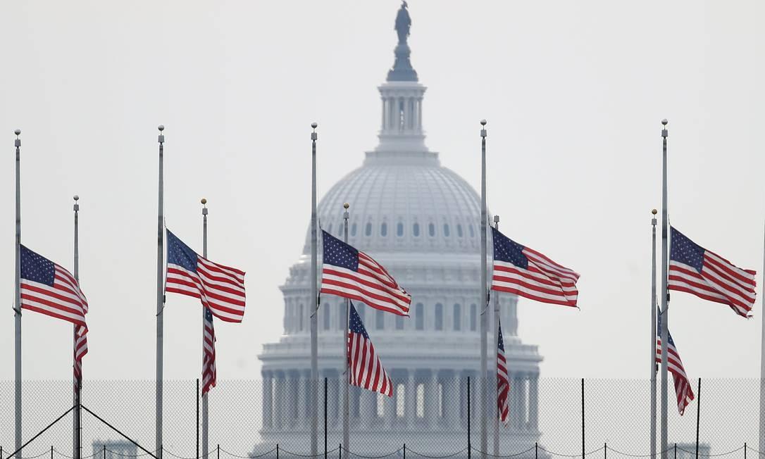Bandeiras dos Estados Unidos, com o Capitólio ao fundo, ficam erquidas a meio mastro em homenagem às vítimas dos ataques recentes em El Paso, no Texas, e em Dayton, Ohio. Dois atiradores mataram 31 pessoas e feriram dezenas de outras em dois tiroteios em um período de 13 horas no fim de semana Foto: WIN MCNAMEE / AFP