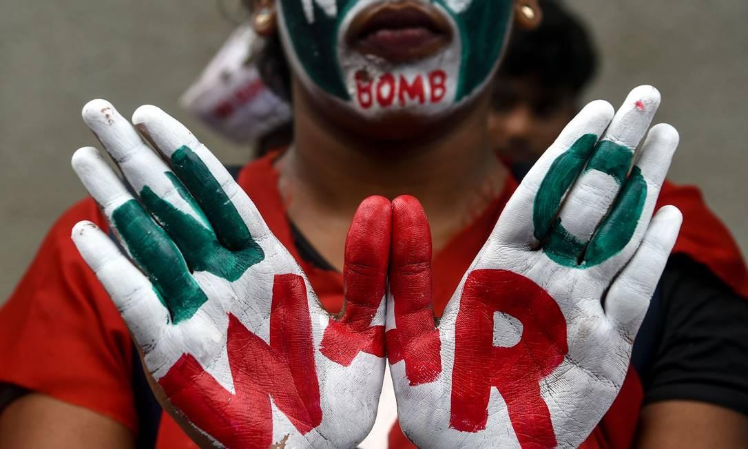 Estudante posa com as mãos pintadas com slogans pela paz durante uma manifestação que marca o Dia de Hiroshima, em Mumbai. O prefeito da cidade pediu ao Japão que assine um tratado da ONU proibindo armas nucleares enquanto a cidade lembra os 74 anos do primeiro ataque atômico do mundo Foto: PUNIT PARANJPE / AFP