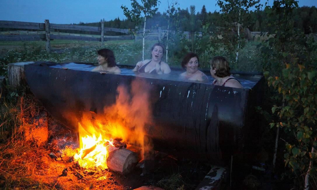 Mulheres letãs tomam banho em uma enorme banheira aquecida por uma fogueira na aldeia de Bobrovka, a cerca de 350 quilômetros de Omsk, Rússia Foto: ALEXEI MALGAVKO / AFP