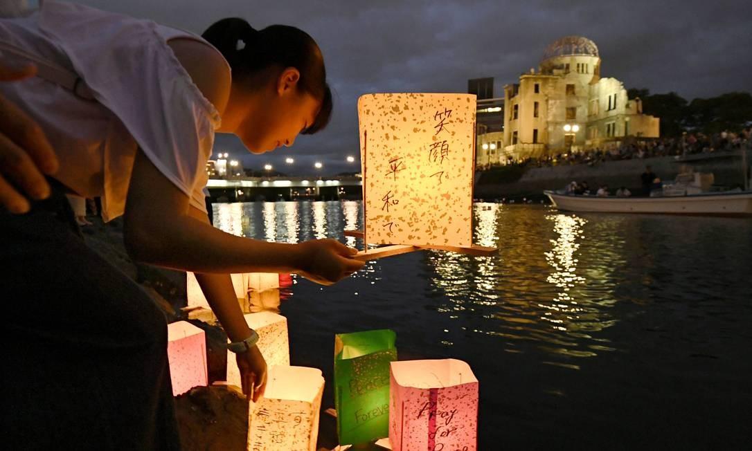 Em Hiroshima, Japão, uma garota lança lanternas de papel no Rio Motoyasu, de frente para a Cúpula da Bomba Atômica eviscerada, em memória das vítimas bombardeio, que completa 74 anos nesta terça-feira 6 Foto: KYODO Kyodo / REUTERS