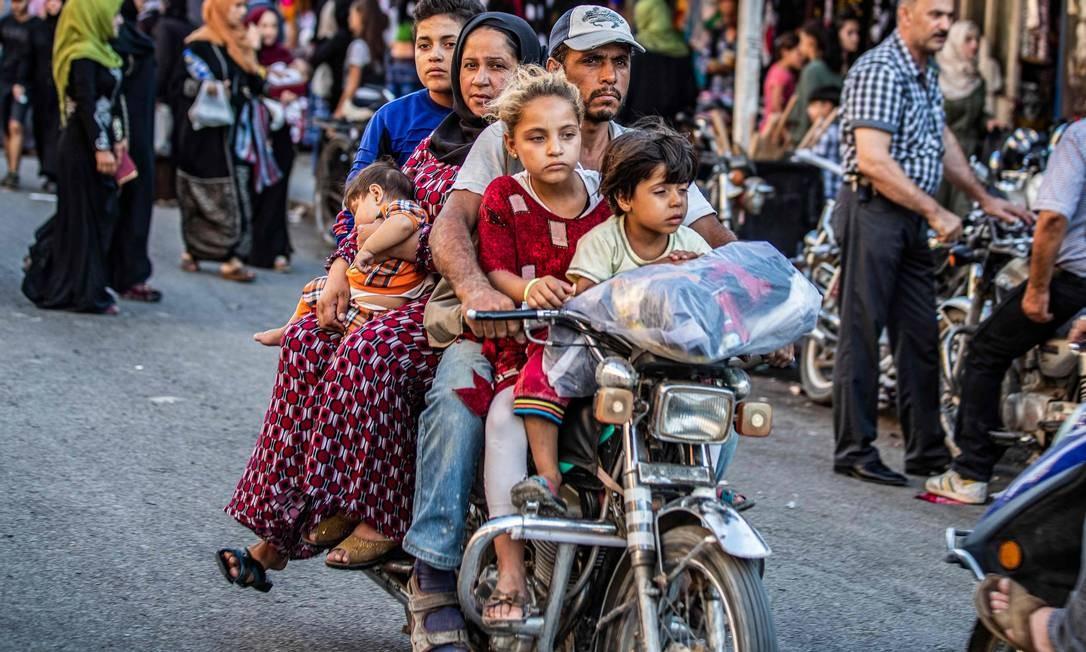 Homem pilota uma moto com uma mulher e crianças em um mercado de rua na cidade predominantemente curda do nordeste da Síria, Qamishli Foto: DELIL SOULEIMAN / AFP
