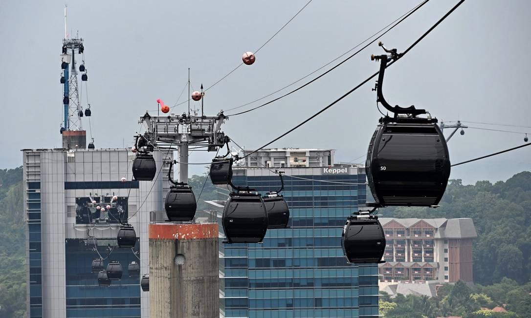 Teleféricos do resort viajam por uma passagem pela ilha de Sentosa, em Cingapura Foto: ROSLAN RAHMAN / AFP