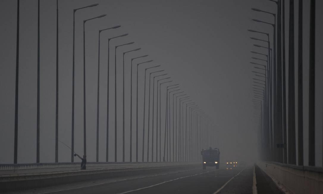 Carros em uma ponte sobre o Rio Angara, em meio à fumaça de incêndios florestais em frente ao assentamento de Boguchany, na Rússia Foto: EKATERINA ANISIMOVA / AFP