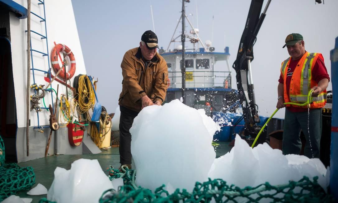 Os tripulantes desgarregam a carga Foto: JOHANNES EISELE / AFP