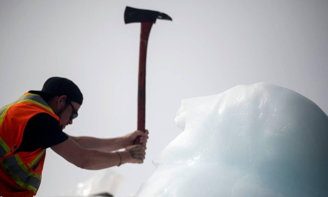 E quebram em pedaços menores com picaretas Foto: JOHANNES EISELE / AFP