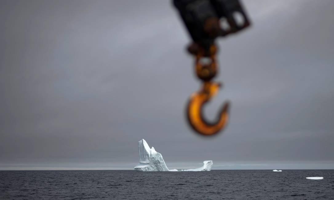 Os maiores são içados para a embarcação, ao fundo um iceberg Foto: JOHANNES EISELE / AFP
