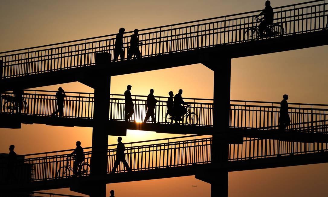 Trabalhadores asiáticos atravessam uma ponte de pedestres em Dubai enquanto se dirigem para trabalhar em um mercado de vegetais Foto: KARIM SAHIB / AFP