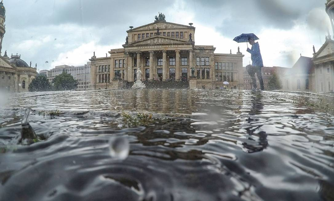 Um forte aguaceiro cai sobre a praça Gendarmenmarkt, com a Konzerthaus (sala de concertos de Berlim, ao centro), o Deutscher Dom (Igreja Alemã, à esquerda) e o Franzoesischer Dom (Igreja Francesa, à direita), em Berlim Foto: PAUL ZINKEN / AFP