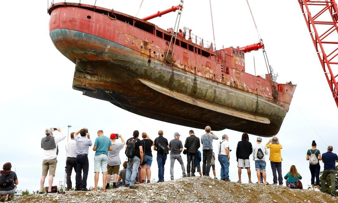 Curiosos assistem ao barco-farol britânico Gannet, construído em 1954 e operado como um farol de South Rock no Mar da Irlanda até o final de 2009, ser retirado do rio Reno, na Basiléia, Suíça Foto: ARND WIEGMANN / REUTERS