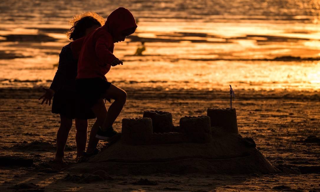 Crianças brincam com um castelo de areia na praia de Gouville-sur-Mer Foto: JOEL SAGET / AFP