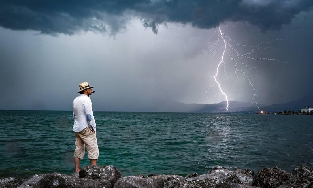 Um homem observa tempestade enquanto um raio cai sobre o Lago de Genebra, perto de Le Bouveret, Suíça Foto: FABRICE COFFRINI / AFP