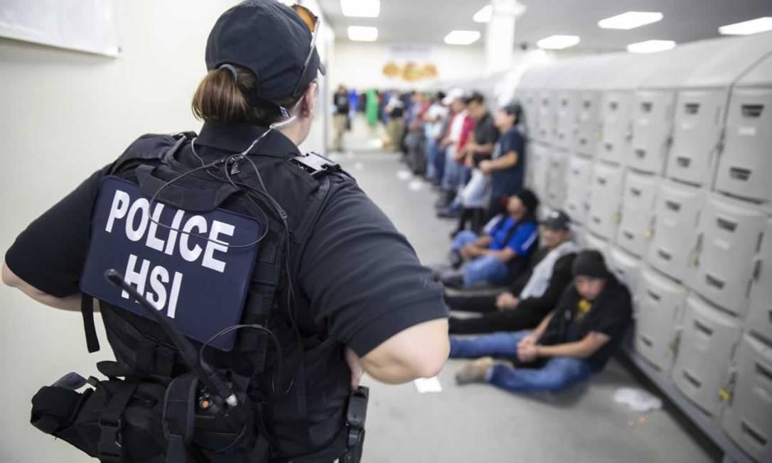 Oficial detém imigrantes ilegais em uma fábrica em Forest, no Mississipi Foto: HO / AFP