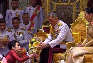 Rei Maha Vajiralongkorn de Tailandia, sentado ao lado de sua esposa, na cerimônia para transformar Sineenat Wongvajirapakdi em sua consorte real Foto: Reprodução / Reuters