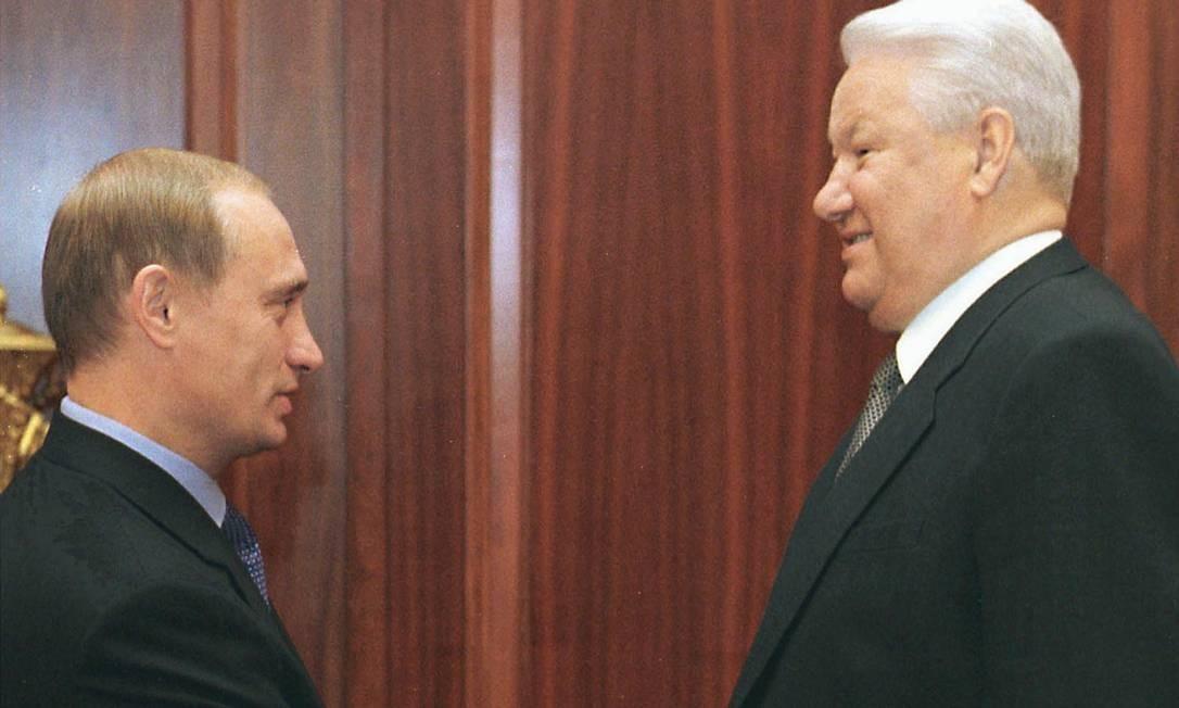 """Em 1999, o então presidente russo Boris Yeltsin (à direita) aperta a mão do primeiro-ministro Vladimir Putin durante sua reunião no Kremlin de Moscou, em 19 de agosto. Debilitado, Boris, que renunciaria em 31 de dezembro em favor do sucessor, explicou na TV que Putin ficaria responsável por """"consolidar a sociedade e garantir a continuidade das reformas"""" e com poder """"sem limites"""" Foto: ELMIRA KOZHAYEVA / AFP"""