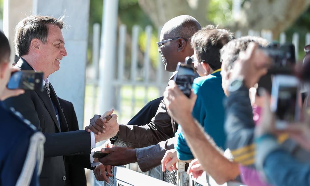 O presidente Jair Bolsonaro cumprimenta populares em frente ao Palácio da Alvorada Foto: Marcos Correa / PR