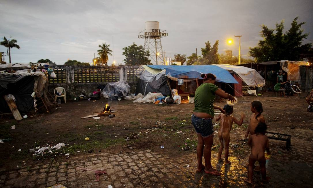 Andréa Pinto dá banho em crianças em terreno baldio que ocuparam. Projeções das autoridades locais e agências humanitárias apontam que 1.500 venezuelanos estão em situação de rua na capital; entre eles, quase 500 têm menos de 18 anos de idade Foto: Daniel Marenco / Agência O Globo