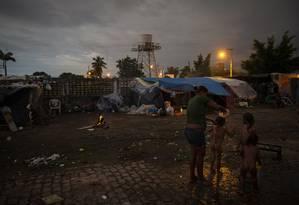 Andrea Pinto dá banho nos filhos num terreno baldio ocupado em Pacaraima: sem lugar em abrigo, famílias vivem em barracas de lona onde também estocam alimentos Foto: Daniel Marenco / Agência O Globo