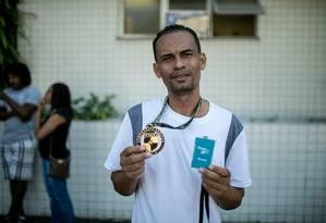 Fabrício, pai de Gabriel, mostra a medalha e a carteirinha do curso que o jovem fazia Foto: BRENNO CARVALHO / Agência O Globo